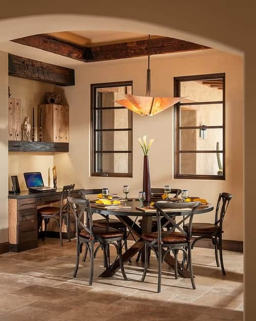 Small dining area with limestone flooring and beige ceiling framed with rustic wood beams. It has a brown dining set that's illuminated by a unique chandelier.