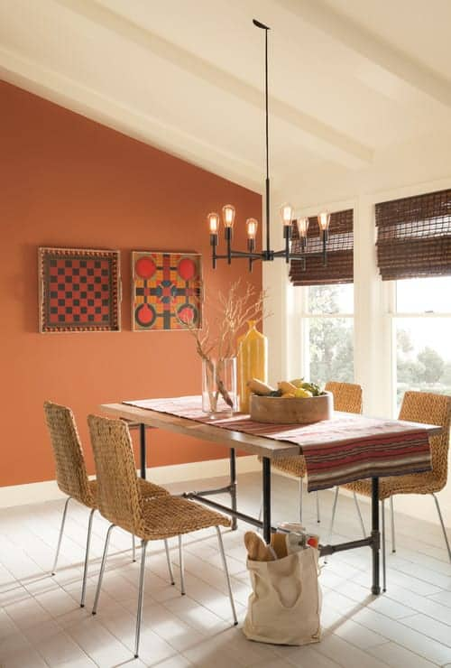 This dining room features a bulb chandelier and eye-catching wall arts mounted on the orange wall. It includes wicker chairs and wooden dining table covered in a red runner.
