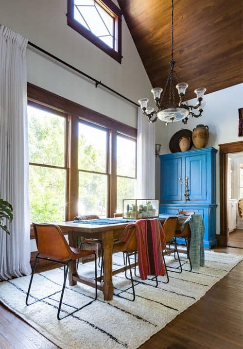 A blue storage cabinet adds a pop of color in this dining room with glazed windows and a cathedral ceiling that matches the hardwood flooring topped by a white rug.