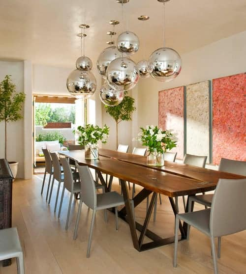 Fresh dining room designed with lovely wall arts and chrome globe pendants that hung over the wooden dining table surrounded with gray chairs.
