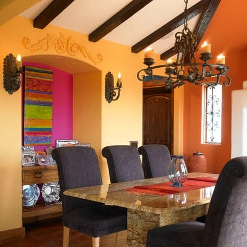Charming dining room boasts a custom dining table and gray chairs lighted by a wrought iron chandelier that hung from the wood beam ceiling. It has hardwood flooring and an arched inset wall that's bursting with colors.