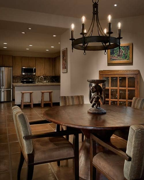 An open dining area showcases a wrought iron chandelier and striped cushioned chairs along with a round dining table topped with wooden sculpture.