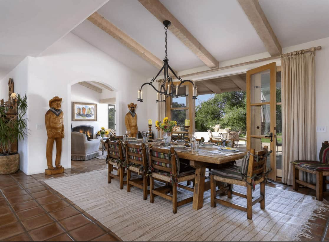 The spacious dining area offers wrought iron chandelier and wooden dining set guarded by tall sculptures. It has a wood beam ceiling and terracotta flooring topped by a tasseled rug.