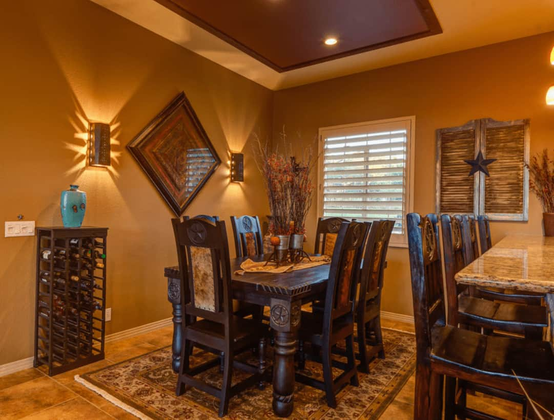 Warm dining room designed with a wooden shutter sealed by a star and a diamond wall art flanked by wall sconces. There's a wine rack across the wooden dining set that sits on a vintage area rug.