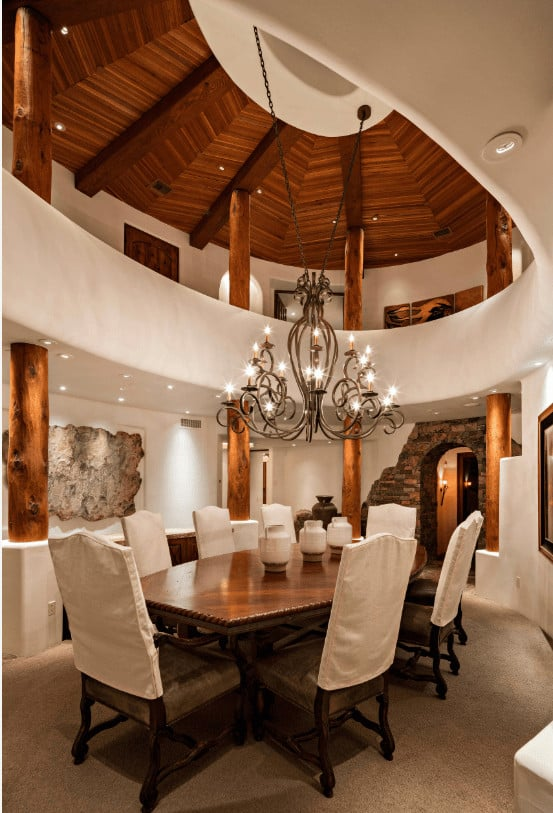 Elegant dining room illuminated by an ornate chandelier that hung from the dome ceiling. It has a boat shape dining table and cushioned chairs surrounded with wooden columns.