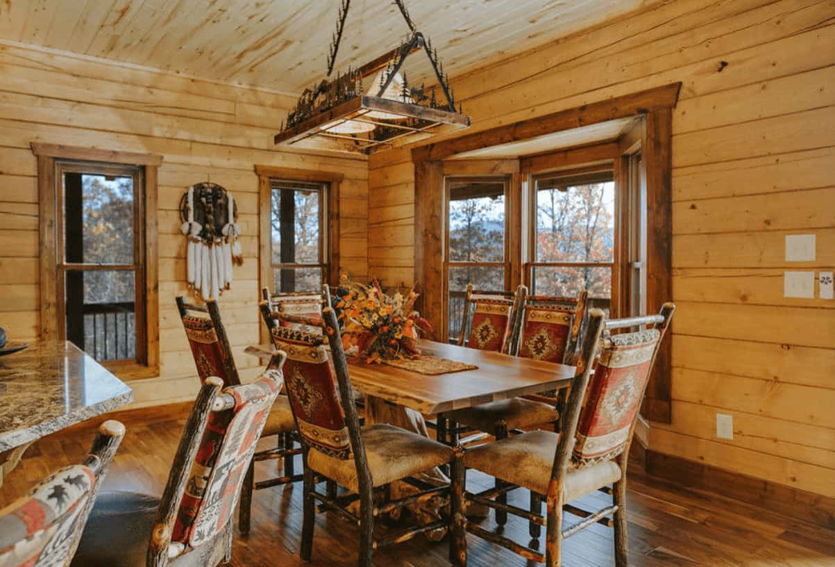 An all wood dining room with a rustic chandelier and tree stump dining table accompanied by matching chairs on wood plank flooring.