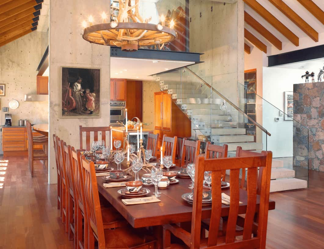 A dining space situated next to the concrete staircase showcasing a round chandelier and redwood dining set that complements with the hardwood flooring.