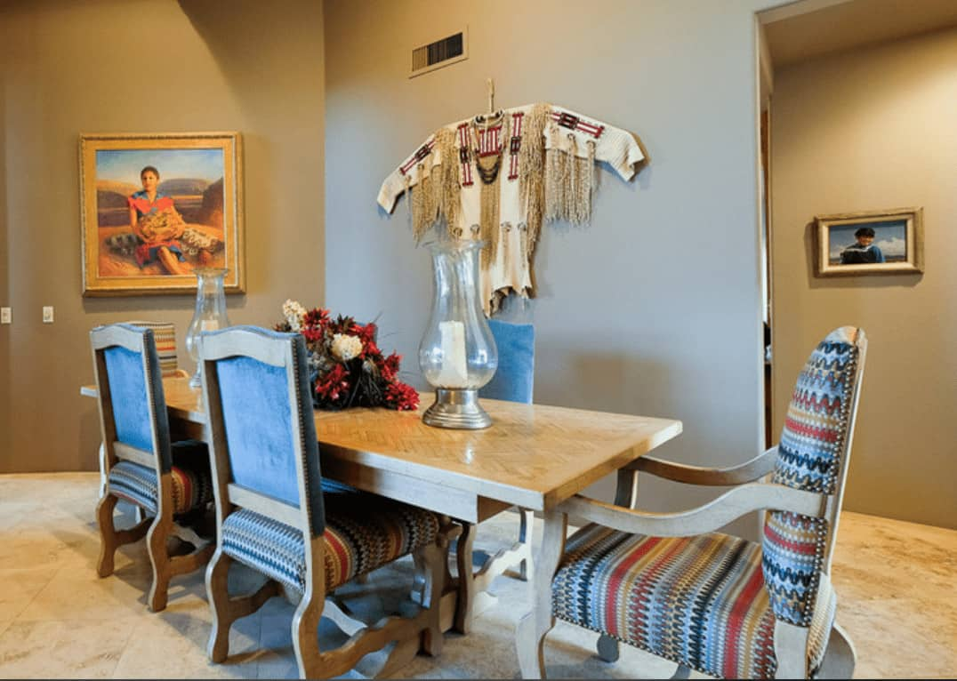 Southwestern dining room decorated with framed photos and an ethnic shirt mounted on the taupe wall. It has cushioned chairs and a wooden dining table designed with a chevron pattern.