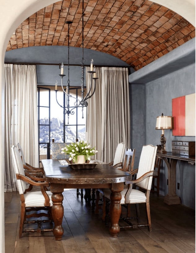 This dining room offers a natural wood buffet table that complements with the wood plank flooring and dining set lighted by a pair of candle chandeliers that hung from the arched ceiling clad in red bricks.