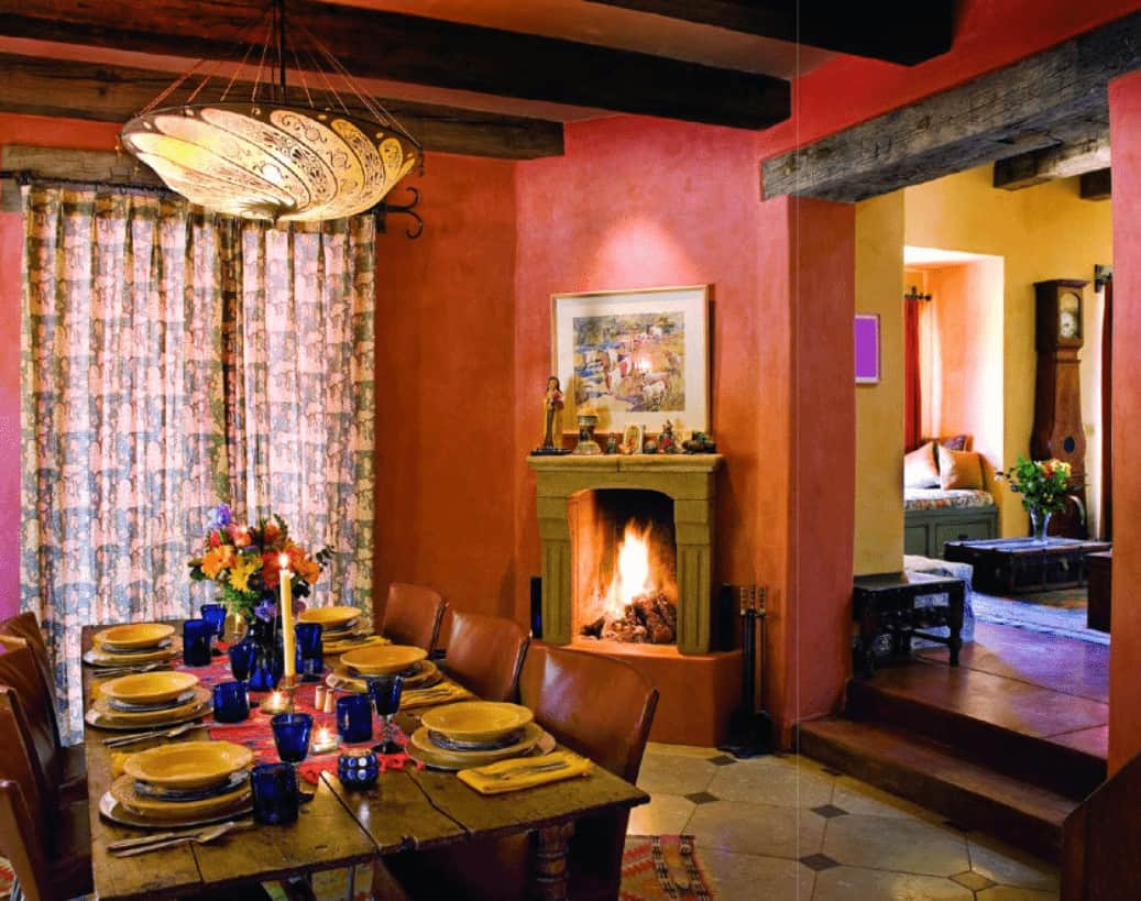 Red dining room with a fireplace and rustic dining table paired with leather chairs. It has tiled flooring and a glazed window covered with patterned draperies.
