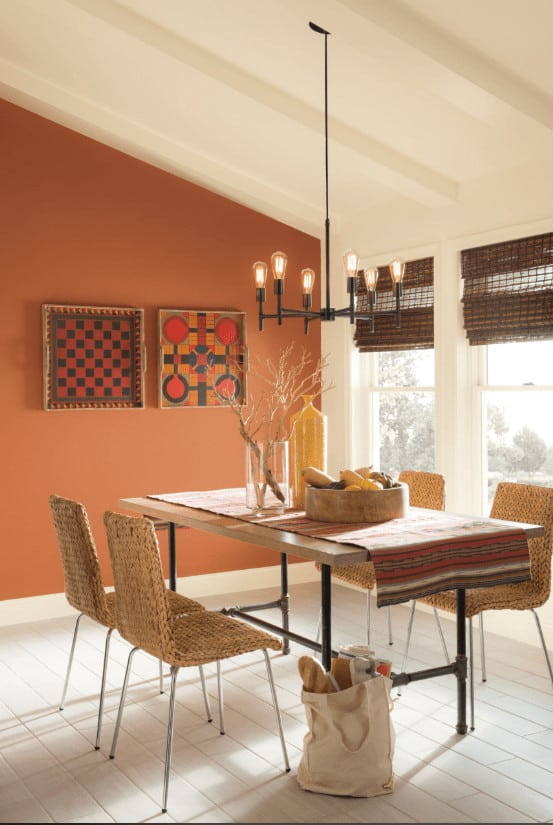 A bulb pendant light hangs over the wooden dining table topped with a striped runner in this dining room boasting wicker chairs and eye-catching art pieces mounted on the red accent wall.