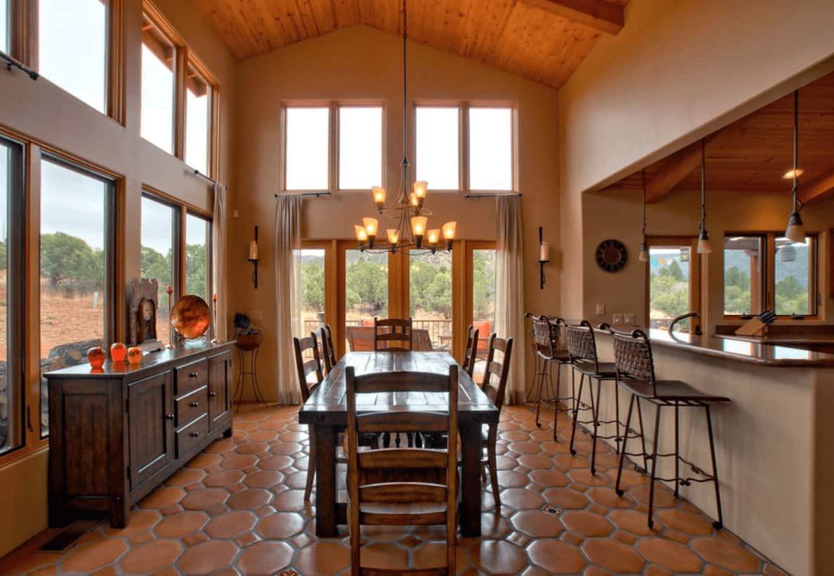 Warm dining room with wooden vaulted ceiling and terracotta flooring arranged in hexagon and diamond patterns. It includes a wooden dining set situated in between a buffet table and bar that's lined with metal counter chairs.