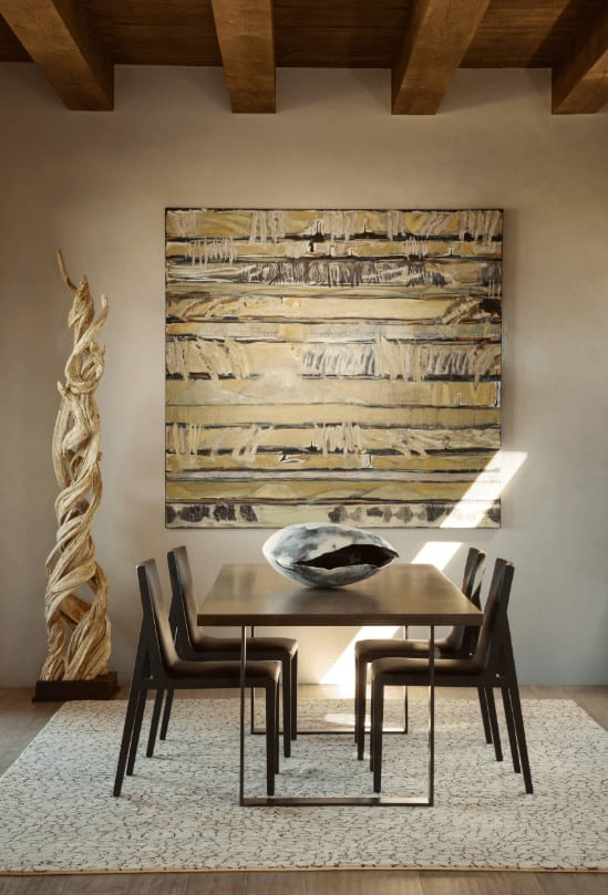 Southwestern dining room designed with a tall wooden decor and interesting wall art mounted across the sleek dining set that sits on a beige area rug.