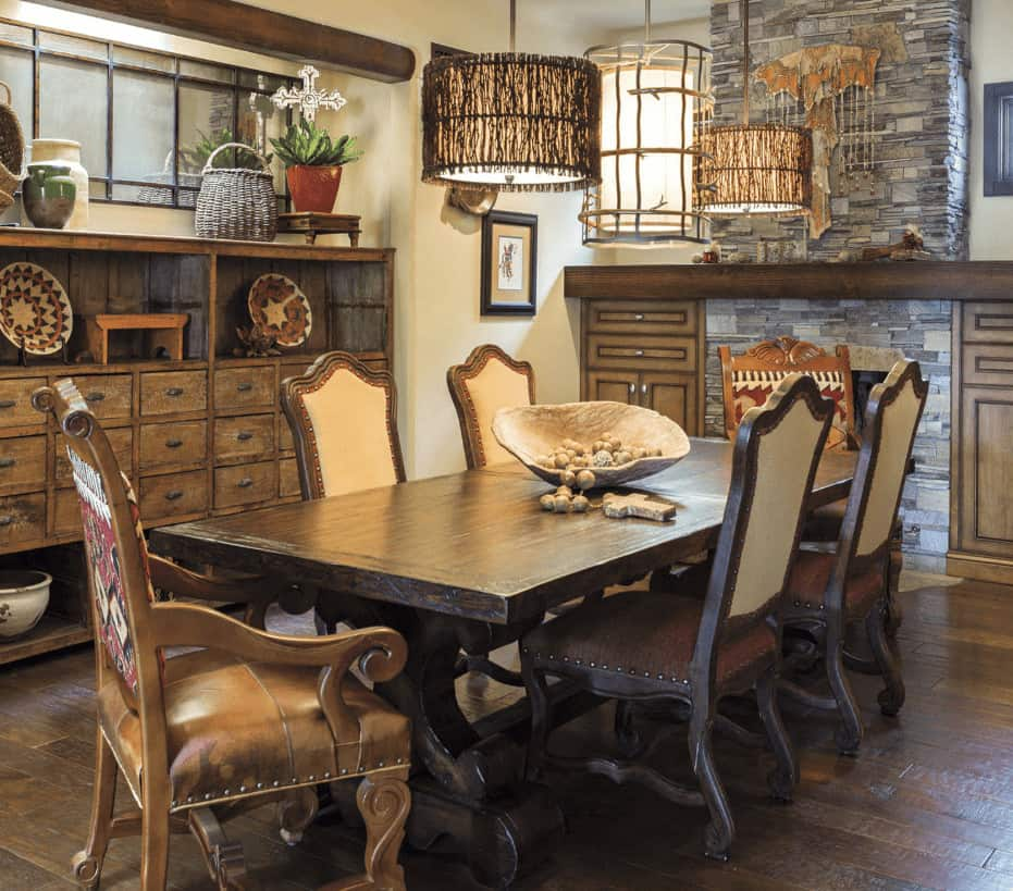 Rustic dining room offers a storage cabinet and wicker pendant light along with upholstered chairs and a wooden dining table topped with a decorative bowl.