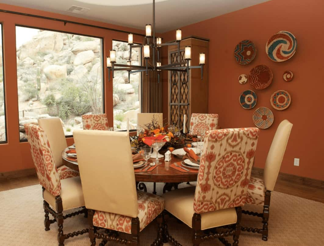 Gorgeous dining room with lovely decorative plates and a wrought iron chandelier that hung over the round dining table accented with alternating printed chairs.