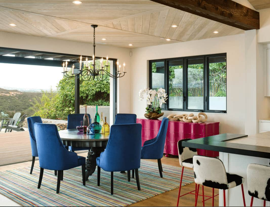 Fabulous dining room with light wood ceiling and hardwood flooring topped by a striped area rug. It includes a pink buffet table and blue chairs surrounding a black dining table that's lighted by a candle chandelier.
