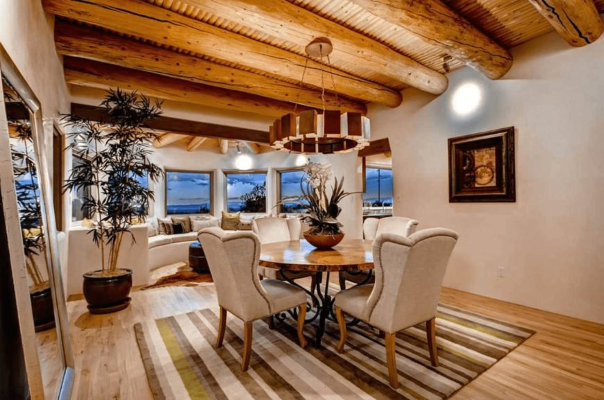 The well-lit dining room features a potted plant and window seat nook that complements the beige wingback chairs on a striped rug. It includes a round dining table and a stylish pendant light that hung from the wood beam ceiling.