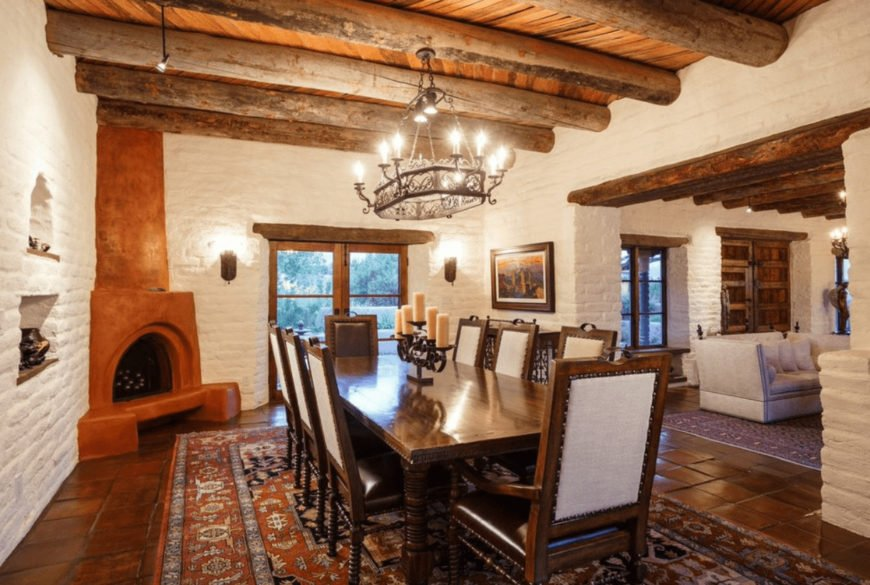 Southwestern dining room offers a dark wood dining set on a classic area rug and a corner kiva fireplace fixed on the white brick walls. It is illuminated by a wrought iron chandelier that hung from the wood beam ceiling.