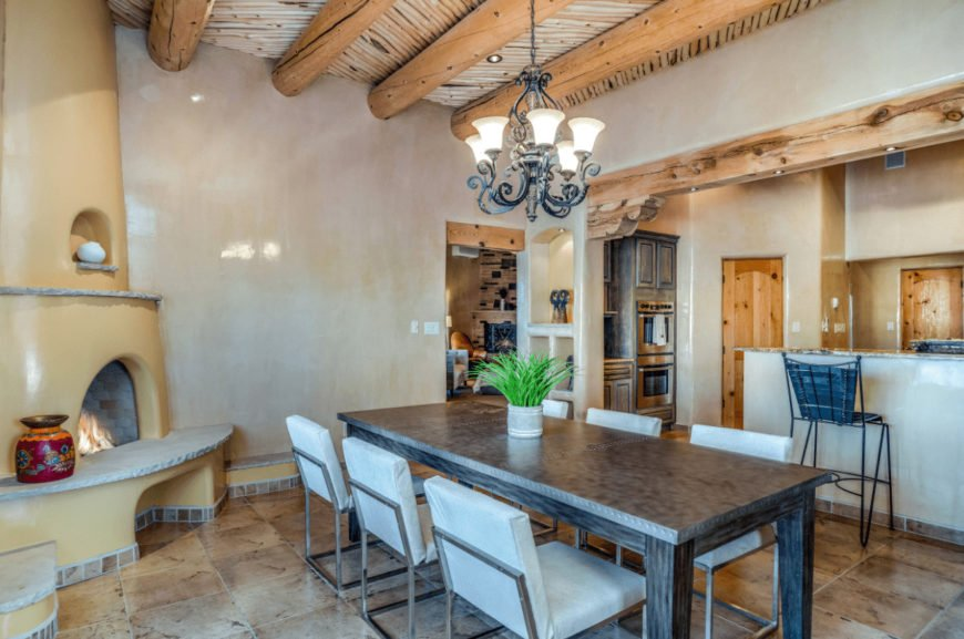 Southwestern dining room showcases a kiva fireplace and a wooden dining table paired with modern metal chairs. It has tiled flooring and wood beam ceiling with a hanging wrought iron chandelier.