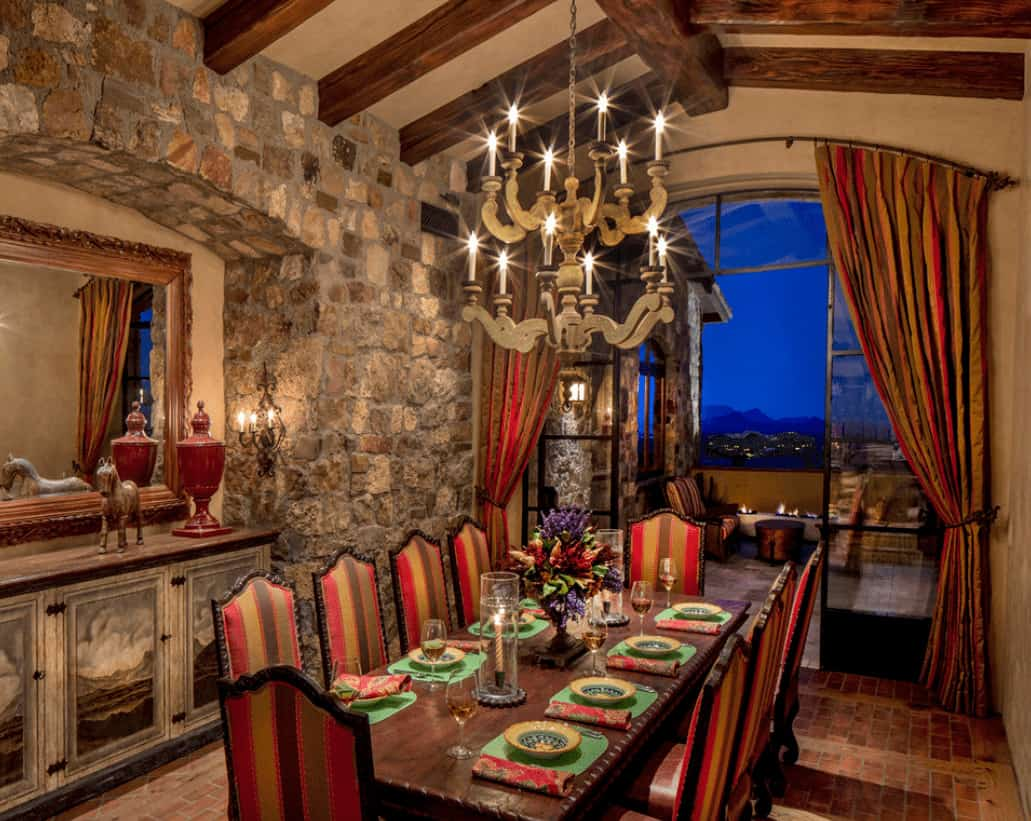 Elegant dining room boasts a stone accent wall and an arched window dressed in striped draperies that complement the high back chairs surrounding a rectangular dining table.