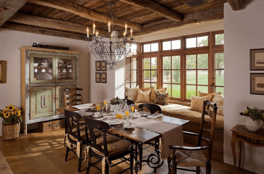 Natural light streams in through the wooden framed windows in this southwestern dining room featuring a seat nook topped with beige cushion and pillows along with a distressed display cabinet across the wooden dining set illuminated by an ornate chandelier.