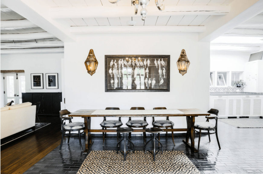 A black framed wall art lighted by warm sconces is the highlight of this white dining room with a wooden dining set accompanied by round back chairs and a pair of stools on a striking diamond pattern rug.