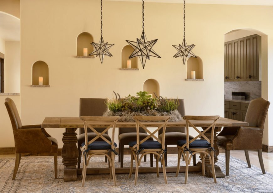 This dining room features arched inset wall niches and star pendant lights that hung over the wooden dining table on a vintage area rug.