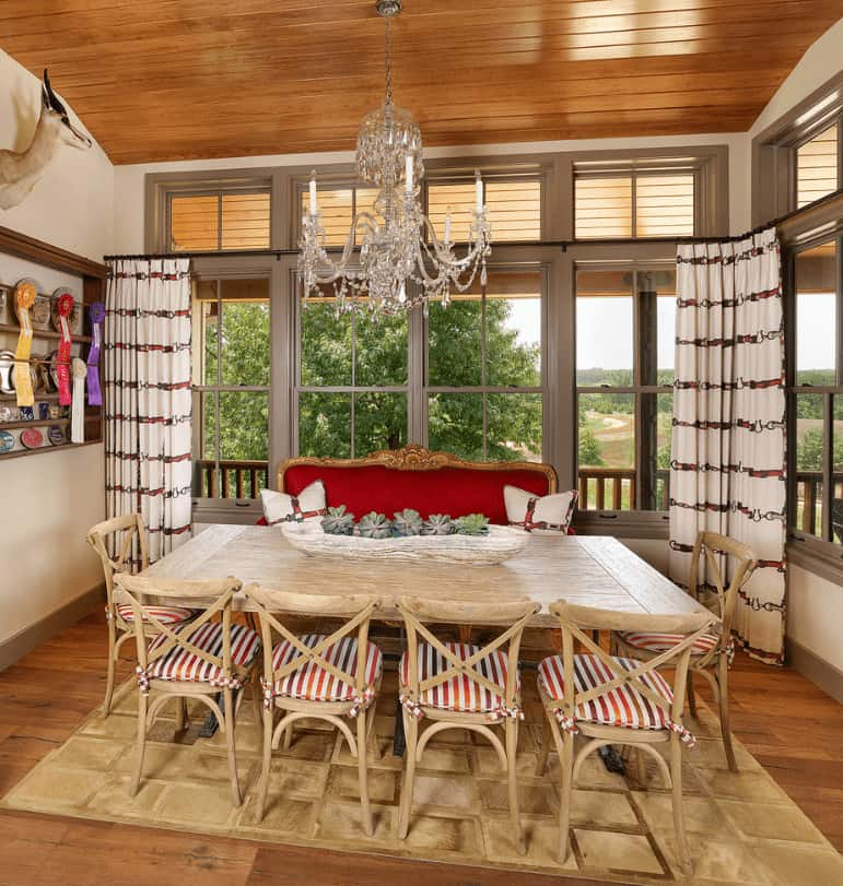 Southwestern dining room showcases wood plank ceiling and flooring along with glazed windows overlooking the outdoor scenery. It has a crystal chandelier and natural wood dining table accompanied by striped cushioned chairs and a classy red bench.