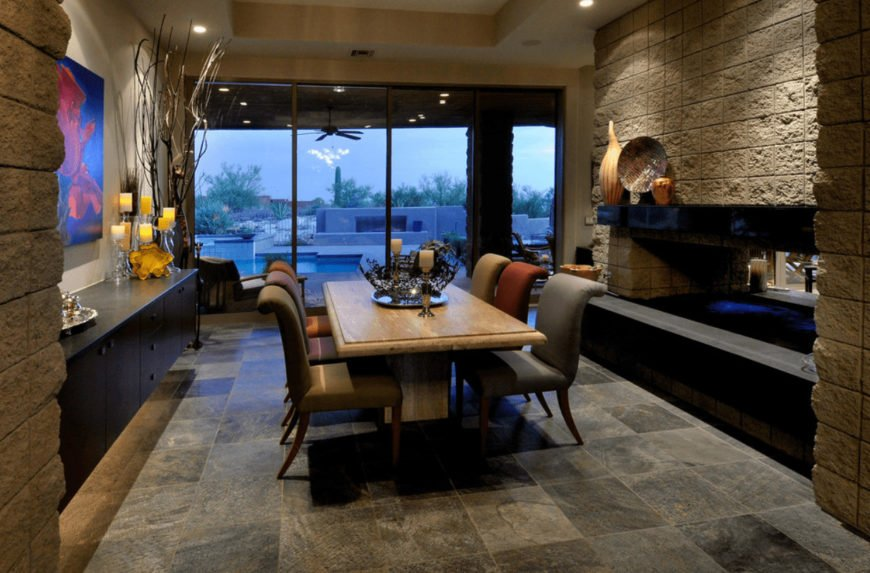 Multicolored dining chairs sit at a light wood table in this dining room with limestone flooring and full height glazing that overlook the sparkling swimming pool.