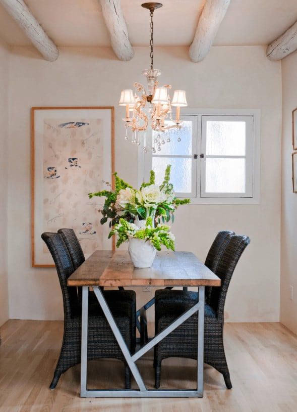 Small dining space with a rustic dining table and black chairs over light wood plank flooring. It includes a gorgeous chandelier and charming wall art mounted next to the white framed window.