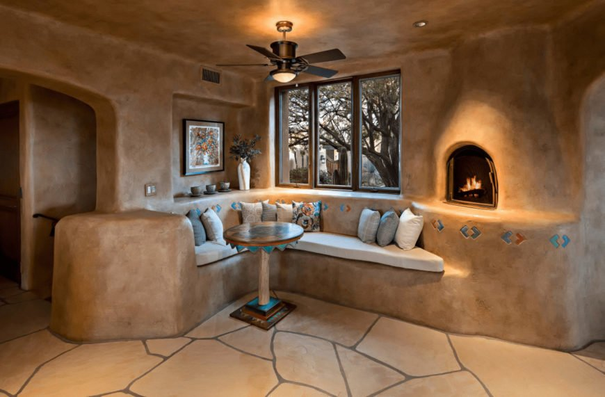 Marvelous dining area by the three-panel window offering a built-in bench and round dining table that sits on flagstone flooring. It includes a fireplace and floral canvas mounted on the inset stone wall.