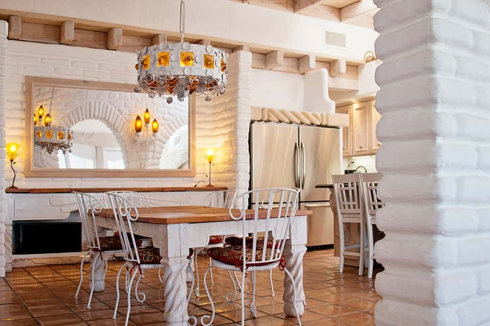 White dining room illuminated by an eccentric chandelier that hung over the wooden dining table and metal chairs. It has terracotta flooring and white brick walls mounted with a rectangular mirror.
