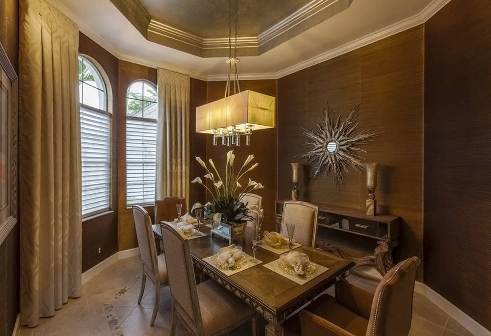 Beige dining room illuminated by a rectangular chandelier that hung from the tray ceiling. It has a classy dining set and a wooden console table accented with a sunburst mirror.