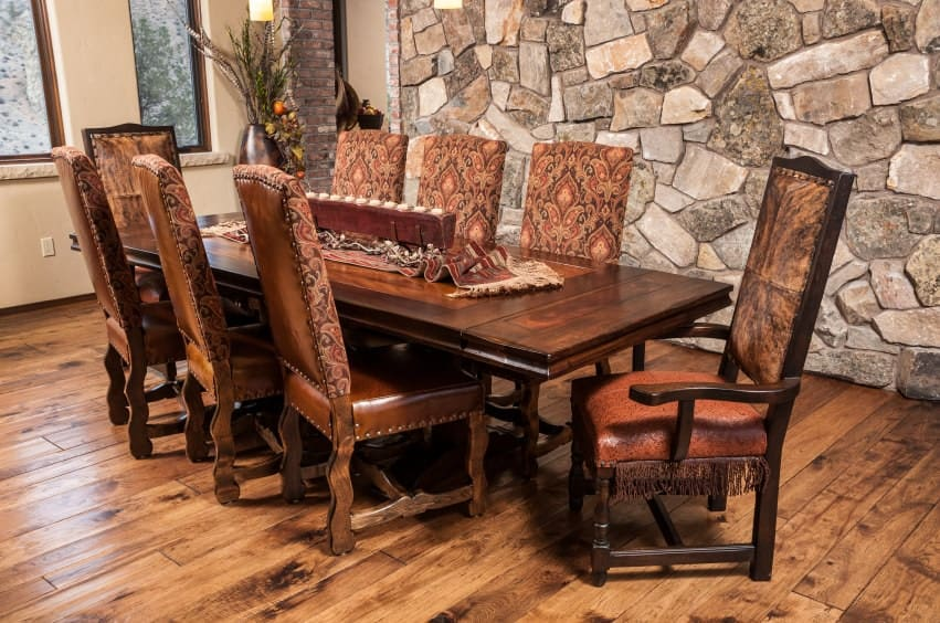 Cozy dining area boasts a wooden dining table and leather upholstered chairs designed with vintage pattern. It has rustic wood plank flooring and a stone accent wall that adds texture in the room.