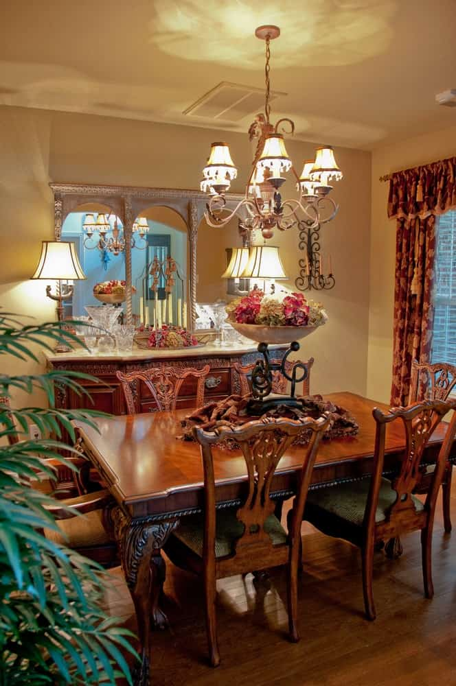 An ornate chandelier hangs over the carved wood dining set in this southwestern dining room offering a wooden buffet table that's topped with white marble counter and three-panel mirror.