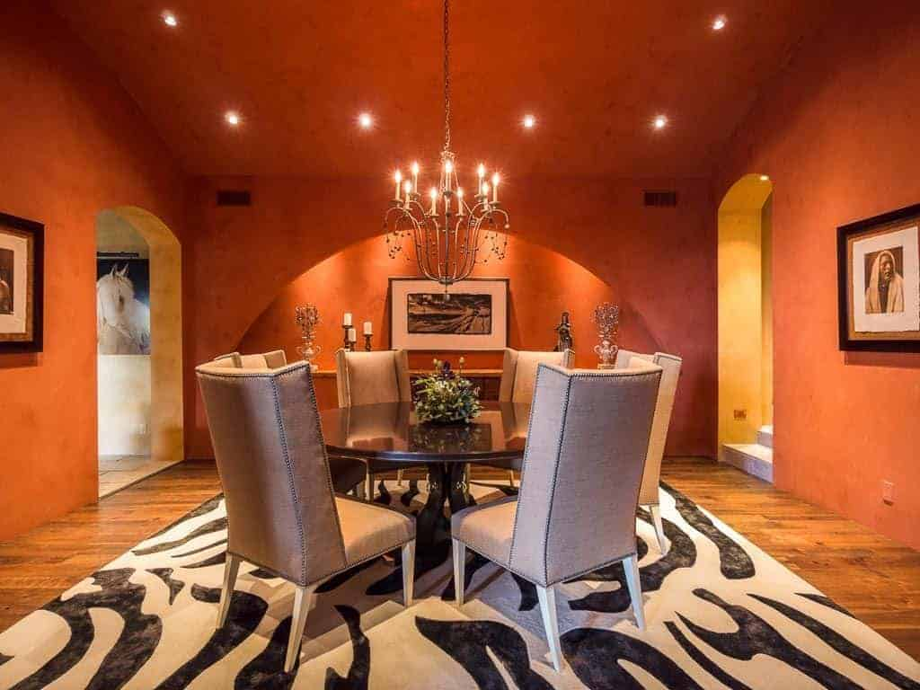 A white printed rug adds a striking accent in this orange dining room lighted by a candle chandelier and recessed ceiling lights. It has a round dining table and beige high back chairs surrounded with black framed photos.