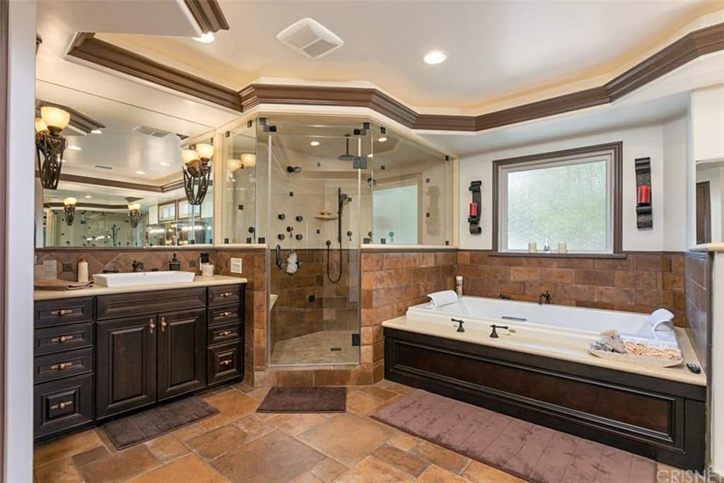 This is a Southwestern-style primary bathroom has some earthy terracotta mosaic tiles for its flooring that extends to the backsplash of the bathtub and the vanity. These two both has the same dark wooden design for its housing and the cabinetry paired with black fixtures and faucets.