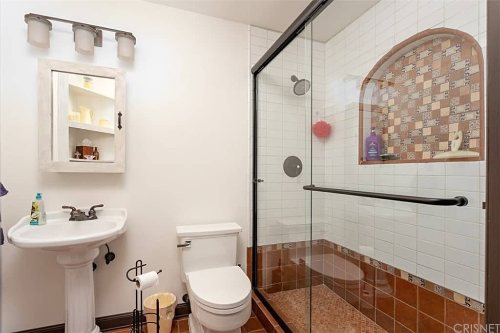The highlight of this simple and homey Southwestern-style bathroom is the charming and earthy chocolate brown tiles of the floor that makes the white toilet and pedestal sink stand out. These earthy tiles extend to the lower walls of the shower area as well as the small alcove on its upper wall.