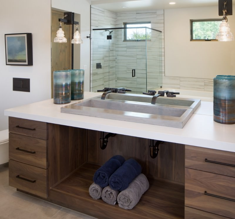 This Southwestern-style bathroom has a glass-enclosed shower area at the corner across from the wooden vanity with a large shelf in the middle flanked by drawers. This is topped with a white countertop and a large frame-less mirror that has wall lamps mounted on it.