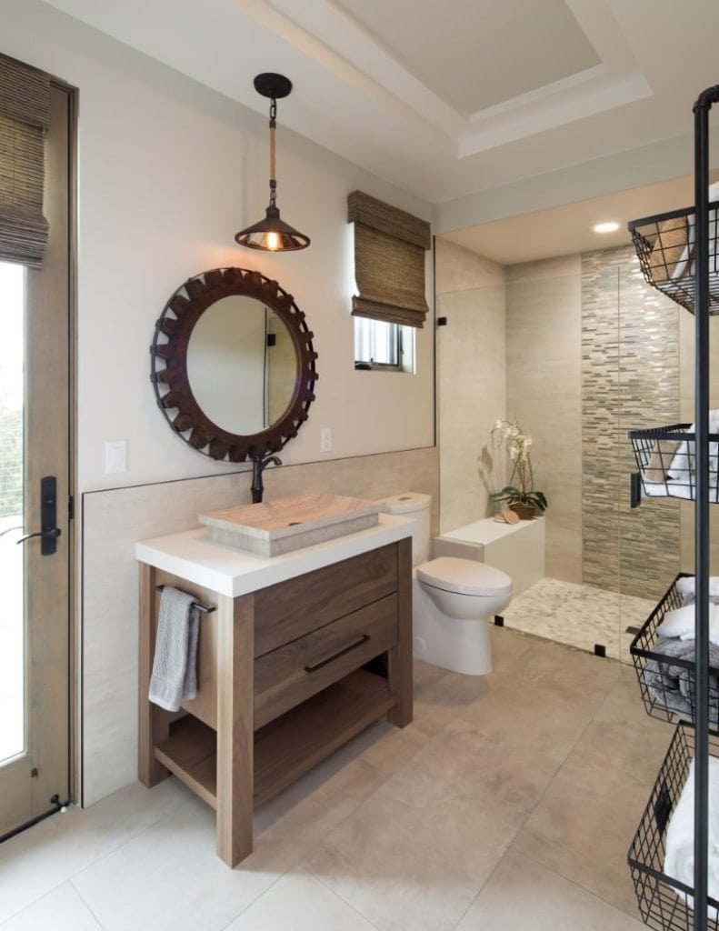 The glass-enclosed shower area has complex patterns running the middle of the beige marble wall that pairs well with the flooring. This bathroom's vanity is paired with a mirror that looks like a large cog wheel that complements the wooden vanity.