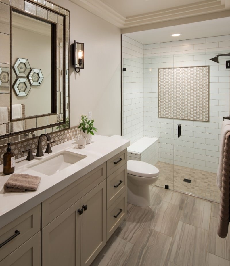 The wall-mounted vanity mirror of this Southwestern-style bathroom has a mirrored frame that gives it a unique look that pairs well with the wall lamp as well as the patterned backsplash that matches with those that adorn the white wall of the shower area.