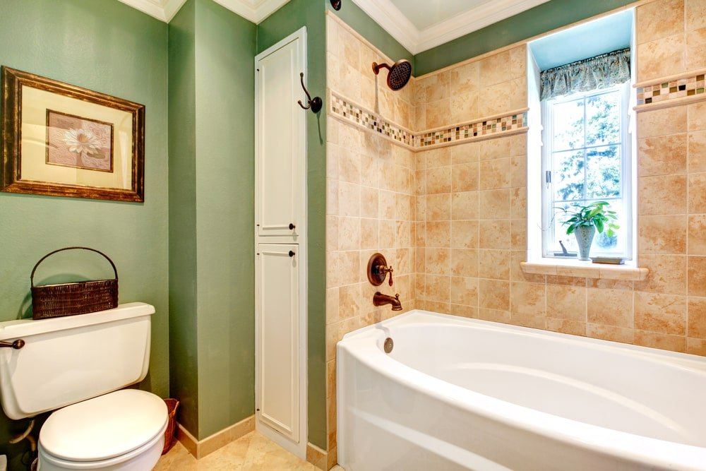 The olive green walls near the white porcelain toilet is a nice complement to the sand-colored tiles of the bathtub area that blends with the floor tiles. This is paired with brass fixtures that contrasts the stark white porcelain bathtub with a small window beside it.