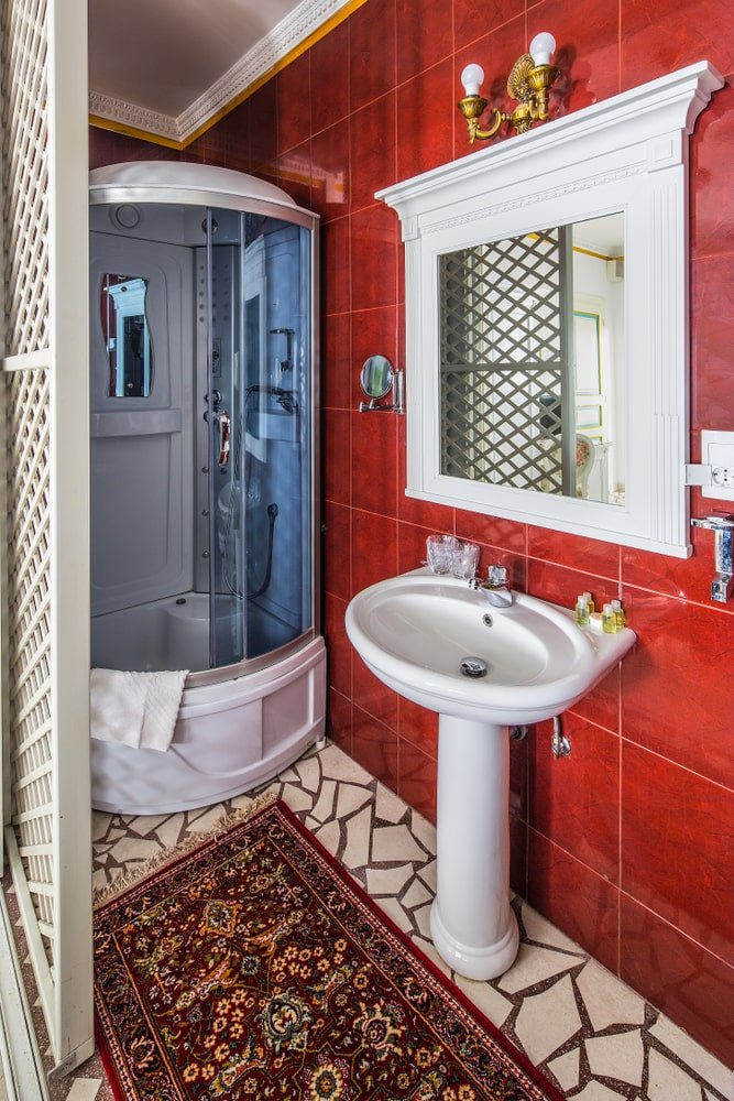 This small and simple Southwestern-style bathroom has earthy red tiles on the walls matching with the red patterned area rug on the flooring that has mosaic white tiles. This rust-colored wall makes the white porcelain pedestal sink stand out as well as the shower area beside it.