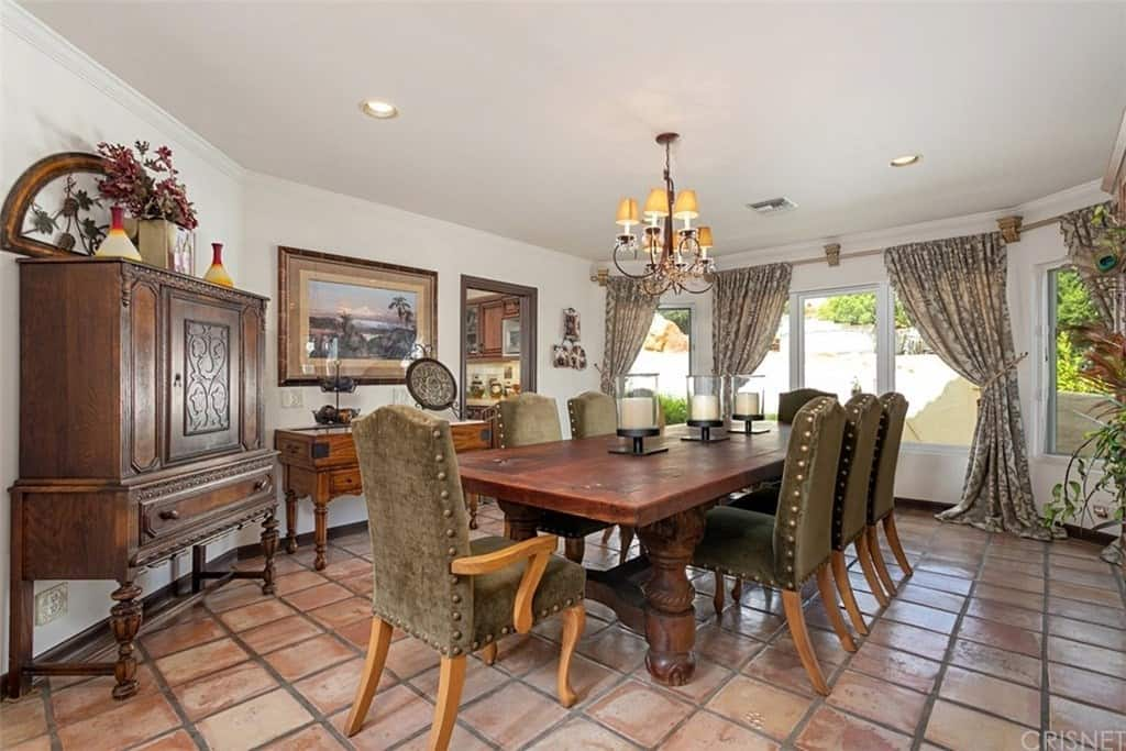 This is a homey Southwestern-style dining room that is complemented by its distressed and worn terracotta flooring tiles. This goes well with the antique vibe of the rectangular dining table, cabinets and the colorful classic painting mounted above the wooden console table.