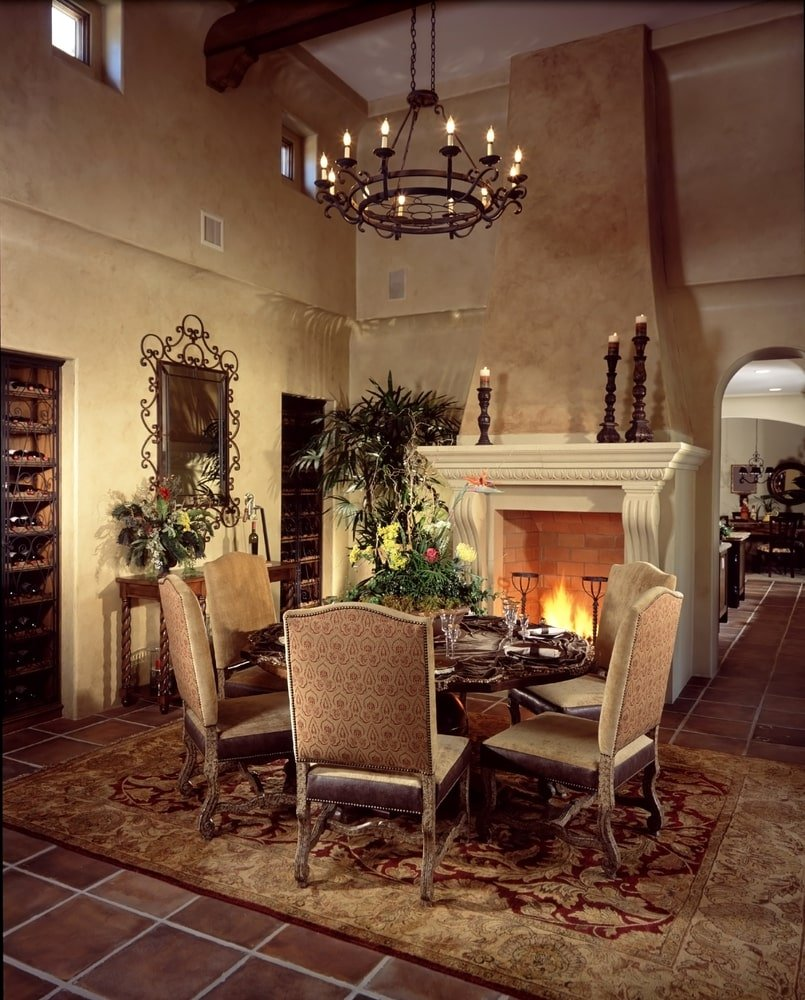 The dark terracotta flooring of this elegant dining room is mostly covered with a red patterned area rug that complements the patterned cushions of the dining chairs around the wooden dining table by the large fireplace that has a beige mantle.