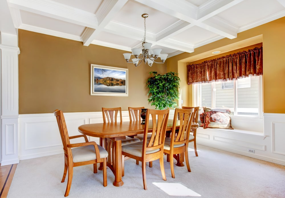 The white tray ceiling and matching white wainscoting is contrasted by the earthy brown walls that complement the wooden dining table and its wooden chairs that have light gray cushions to match the carpeting of the Southwestern-style dining room.
