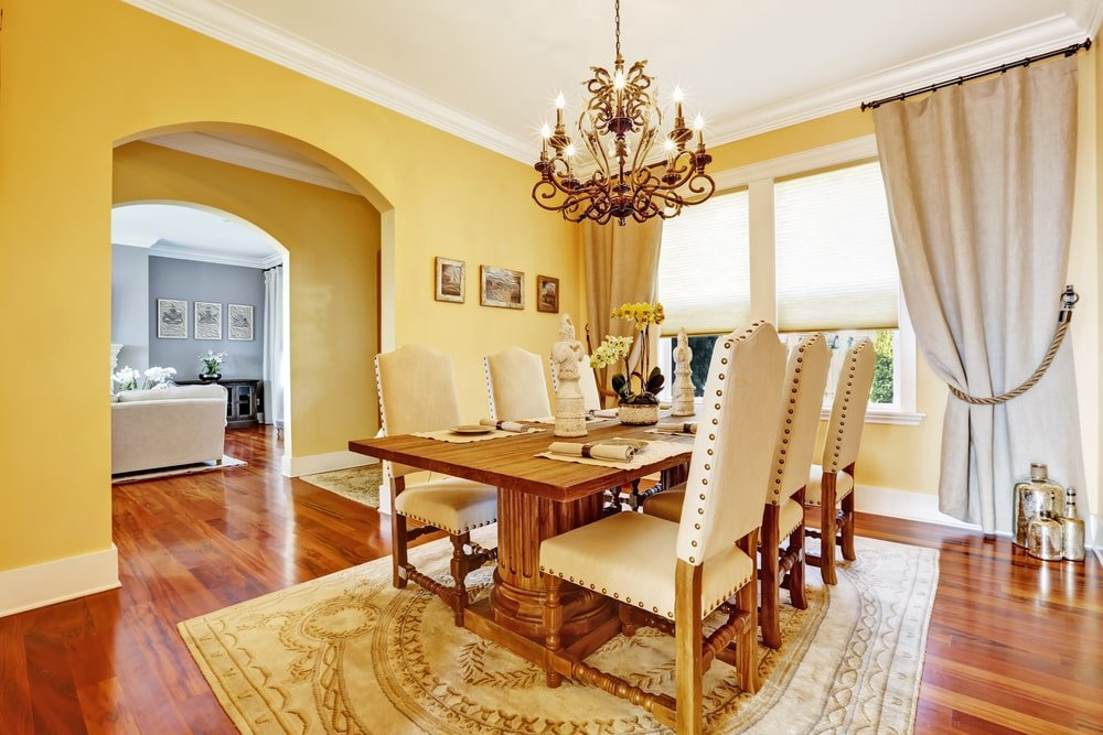 The elegant patterned area rug over the slick and shiny hardwood flooring matches with the yellow walls of this Southwestern-style dining room. This is brightened by the white ceiling as well as the natural lights coming in from the window and the wrought iron chandelier.