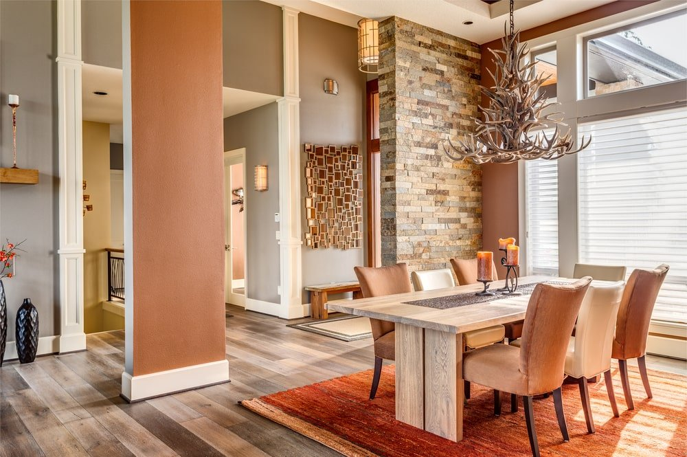 The highlight of this Southwestern-style dining room is the charming and unique antler chandelier hanging over the wooden rectangular dining table that is paired with cushioned chairs with an earthy tone matching the rust colored area rug underneath.