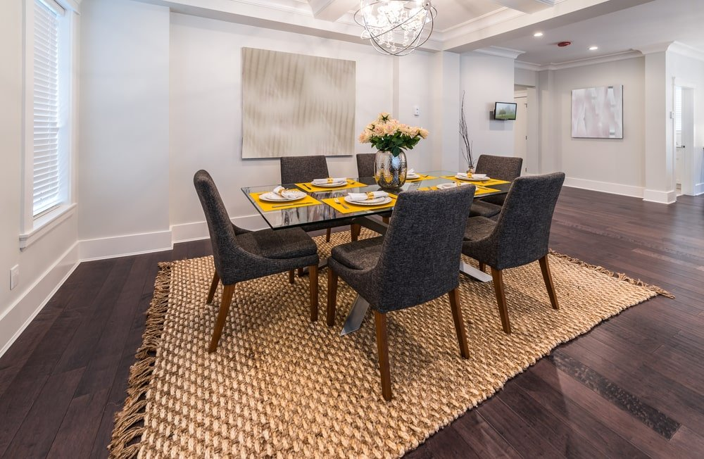 The beautiful woven area rug dominates the dark hardwood flooring that contrasts the elegant white walls. These are brightened and enhanced by the white lights of the brilliant chandelier of the white tray ceiling. This makes the dark gray cushioned chairs stand out.