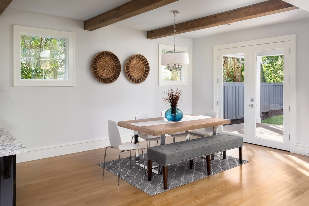 This simple Southwestern-style dining room has a wide hardwood flooring that matches the wooden top of the modern dining table. This is paired with a cushioned gray bench and modern white chairs matching the white walls adorned with a couple of woven wicker decors.